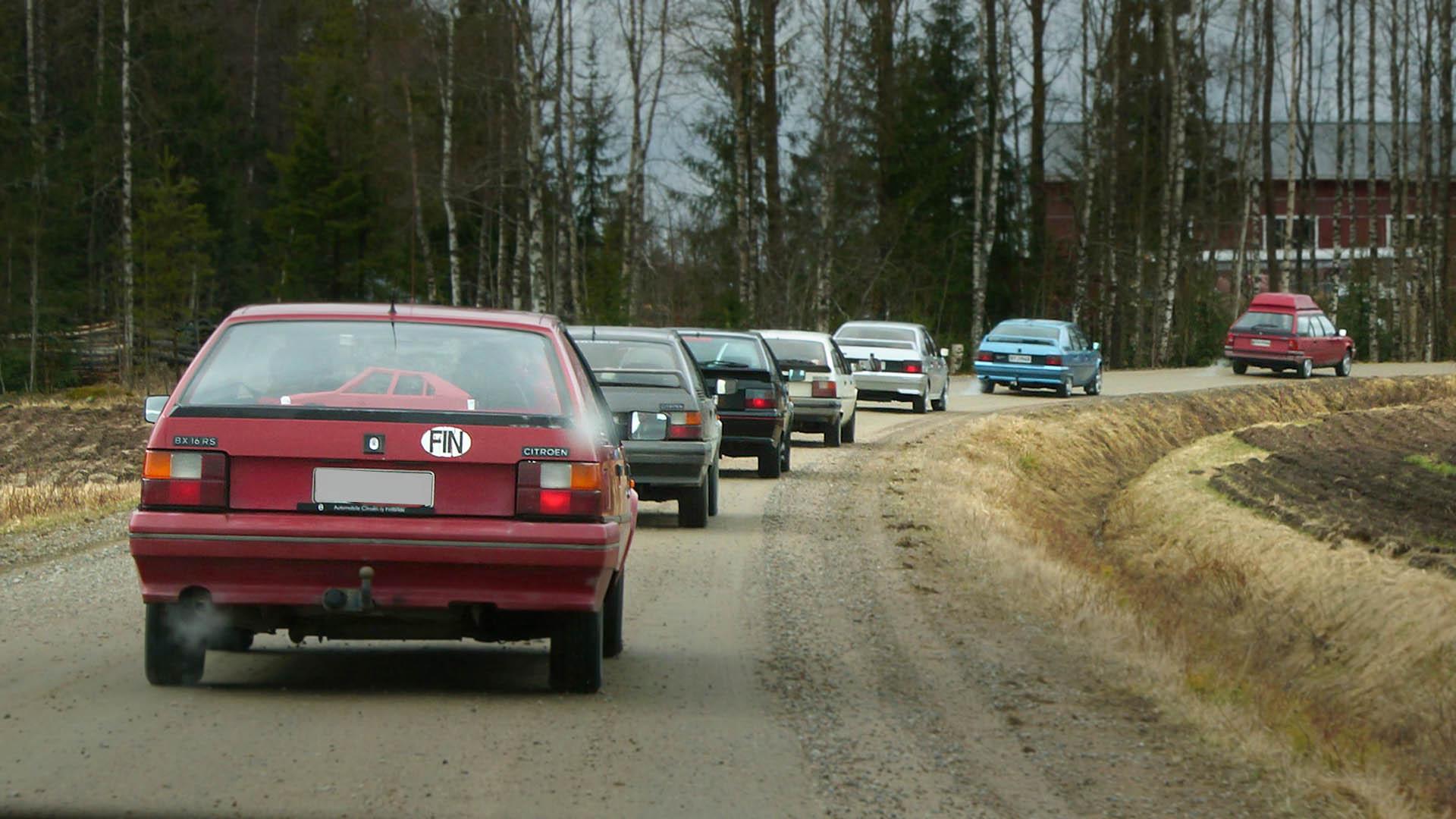 Citroën BX -autoja ajaa jonossa soratiellä maaseudulla.