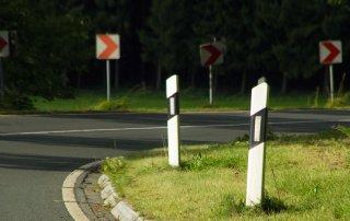 Oikealle kaartava asfalttitie jossa etualalla kaksi valkoista opastinpylvästä ja taustalla vaarallisesta mutkasta kertovia liikennemerkkejä.